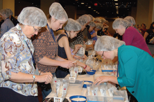 Rotarians pack meals for the homeless at a district conference session