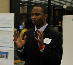 A student presents his papers at One World Education's Fair